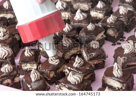 decorating cake with whipped cream with piping technique - stock photo