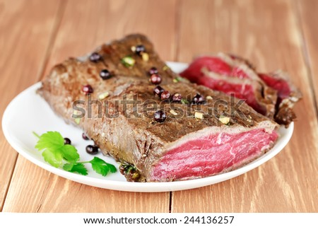Delicious dinner of rare roast beef with cilantro on white plate - stock photo