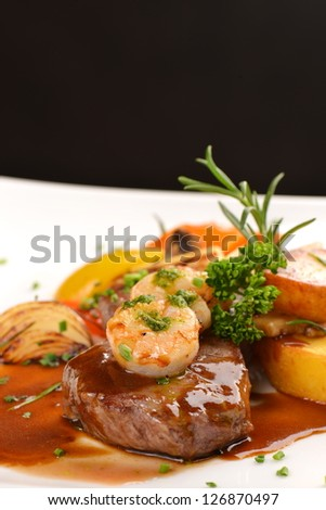 Delicious juicy barbecued steak and prawns with grilled tomato and roasted potatoes. Surf and Turf style. Shallow dof - stock photo