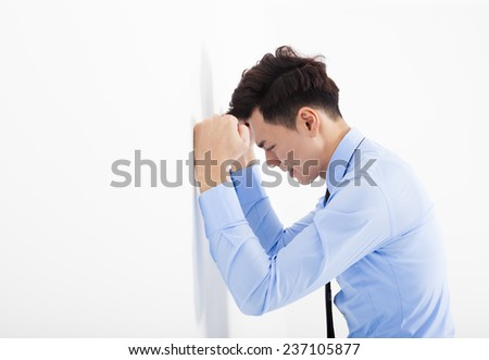 depressed young business man  leaning at the wall in office - stock photo