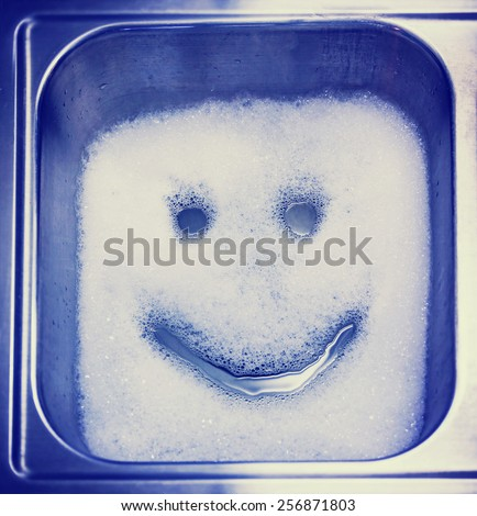 Detergent or soap bubbles and water in the shape of a smiley face in a sink toned with a retro vintage instagram filter effect app or action - stock photo