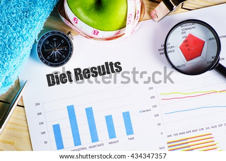 """""""Diet Results"""" black text on paper with magnifying glass on red spider bar on wooden table with compass, pen, towel, green apple with measurement tape, and whistles - fitness, diet and healthy concept - stock photo"""