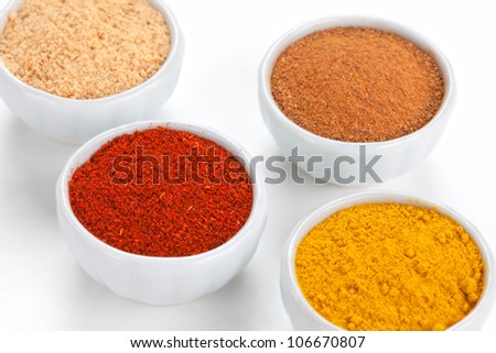 Different spices in white bowls isolated on white background. Paprika, Curry, Black Pepper, Ginger, Cinnamon, Bay Leaves. - stock photo