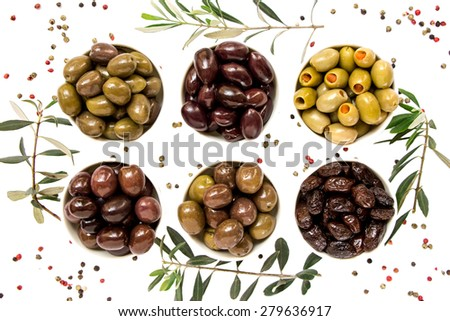 6 different types of olives in white cups framed by olive branches and scattered spices on white background. 2 rows of 3 cups. Olives green, black, green with pepper. The variety of olives. Top view. - stock photo