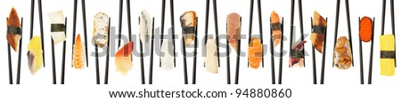 18 different types of sushi being held up in in a criss-cross line with black chopsticks isolated on white. - stock photo