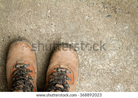 Dirty hiking boots, on concrete floor. - stock photo