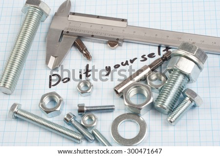 """""""Do it yourself"""" - Screw, Nuts and caliper on  graph paper background - stock photo"""