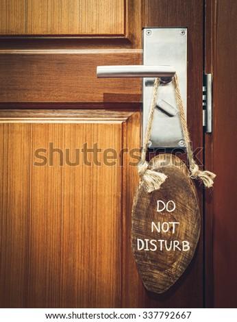 """do not disturb"" sign hanging on the doorknob - stock photo"