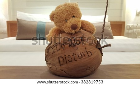 """Do not Disturb"" sign message stamp on coconut with bear doll in the comfortable bad  - stock photo"