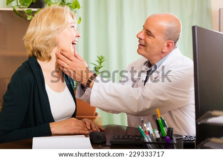 Doctor checking thyroid of mature woman  - stock photo