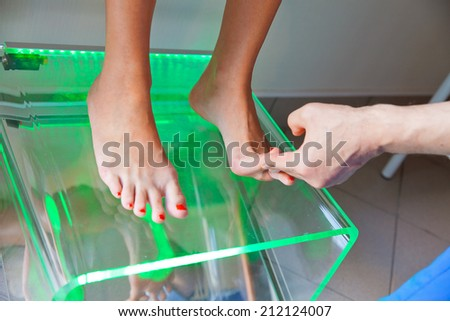 doctor orthopedist examining feet using Plantoscopy in his office - stock photo