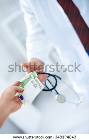 Doctor's hand in glove receives money, concept corruption in health care
