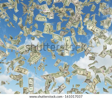 1,5,10,20,50,100 dollar bills falling from blue sky. - stock photo