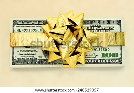 100 dollar bills wraped up with a gold ribbon  - stock photo
