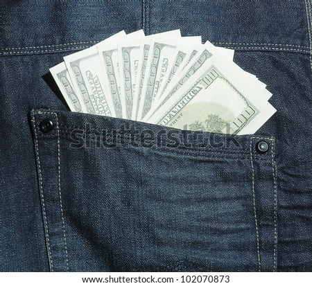 100 dollars banknotes into hip-pocket of jeans. - stock photo