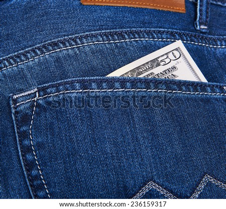 50 Dollars bill sticking out from a blue jean pocket. Closeup - stock photo