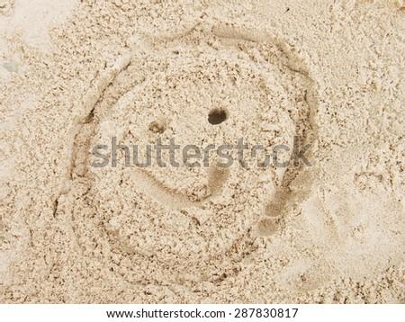 Drawn face in summer beach sand.  - stock photo