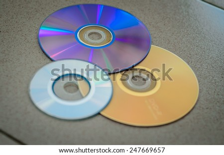 3 DVD-roms with different colours scattered on the floor. - stock photo