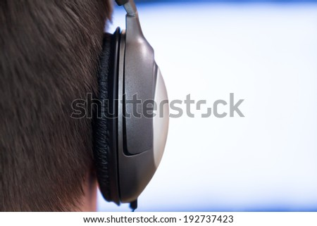 Earphone closeup on glowing background monitor - stock photo