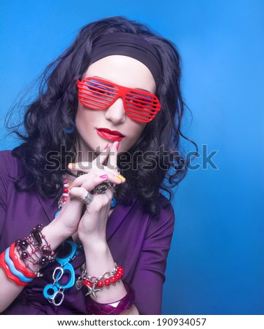 80-ears style. Young woman with bright visage and in violet dress and sunglasses - stock photo