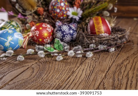 easter eggs in the nest, decorative butterfly, flowers and blooming willow. blurred. on the wooden background. easter decoration. happy easter. blurred - stock photo