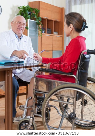 elderly doctor signing documents with   woman in   wheelchair. - stock photo