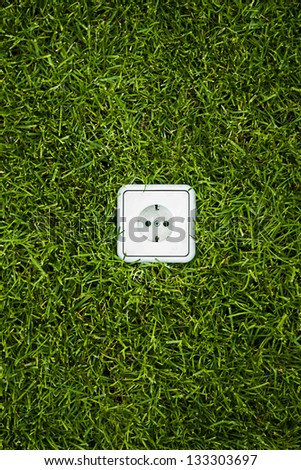Electric socket in grass - stock photo