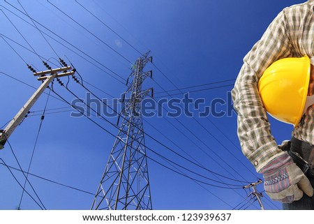 Electrician and  high voltage power transmission line tower with a pole - stock photo