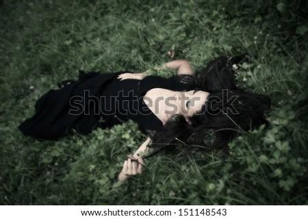 elegant  woman in long black dress lie in grass  full body shot - stock photo