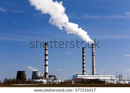 emissions from industrial plants against the blue sky. - stock photo