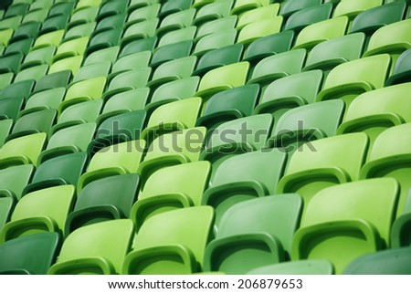 Empty bleachers at stadium. Endless rows of green plastic seats. Seating rows in a stadium with weathered chairs - stock photo