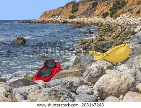 2 empty bright red and yellow kayaks with black seats waiting on rocky shore. Big boulders, blue ocean water, cliff in background.  - stock photo