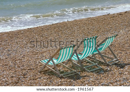 3 empty deck chairs on the beach - stock photo