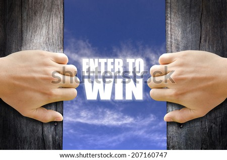 """Enter to Win"" text in the sky behind 2 hands opening the wooden door. - stock photo"