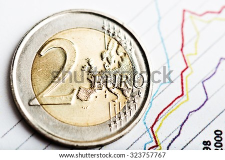 euro coin on fluctuating graph. Rate of euro (shallow DOF) - stock photo