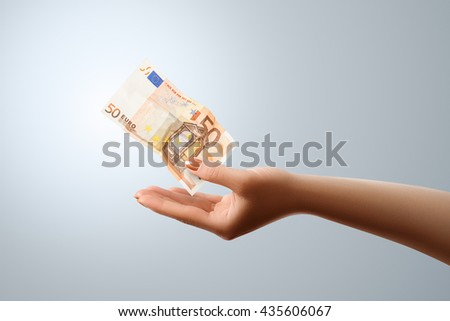 50 Euro flies to the female hand. Conceptual business image - stock photo
