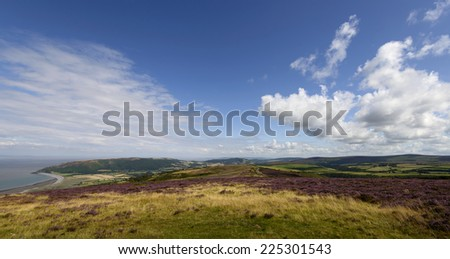 Exmoor panorama,  landscape with moor vegetation, in background the hilly countryside and the coastline  - stock photo