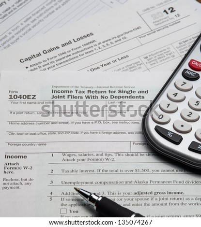 2012 1040 EZ Tax and assorted Forms with a pen and calculator - stock photo