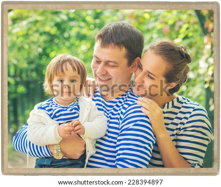 family father playing with baby on nature vintage card - stock photo