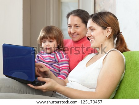 Family of three generations sits on the sofa with laptop - stock photo