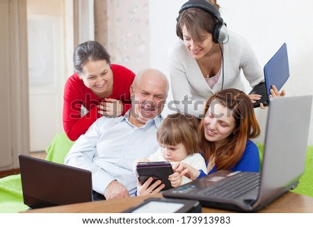 family of three generations uses few various electronic devices in home interior  - stock photo