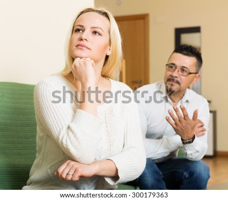 Family quarrel. Sad guy and angry woman during quarrel  in living room  - stock photo