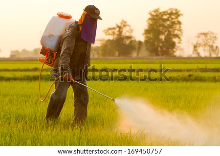 Farmer spraying pesticide - stock photo