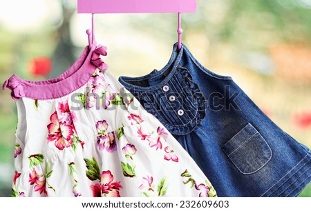 Fashion baby dresses  hanging on a hanger on a green  summer background - stock photo
