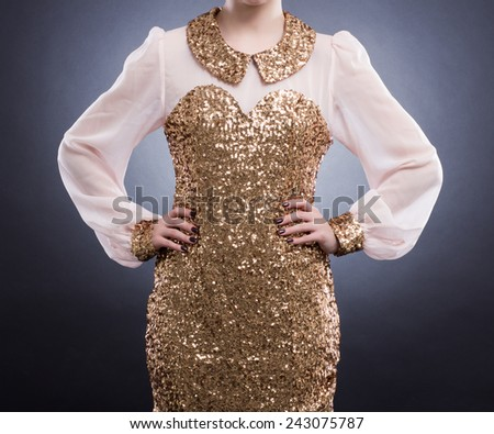 Fashion Image. Beautiful elegant dress with gold sequins on the young woman. - stock photo