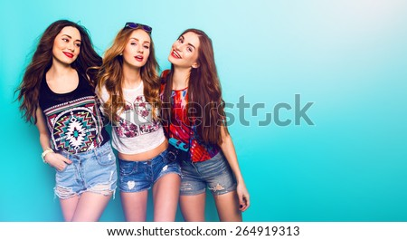 Fashion portrait of   Three best friends posing in studio, wearing summer style outfit and jeans shorts against blue  wall . Girls smiling and having fun. - stock photo