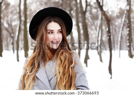 fashion portrait of young romantic dreaming hipster girl in grey coat and black hat. Photo toned style instagram filters - stock photo