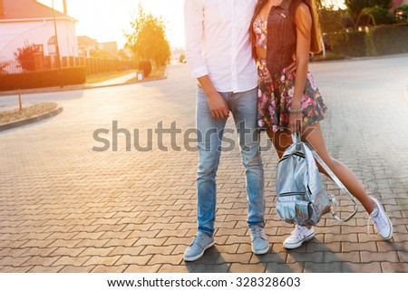 Fashion summer  portrait of Couple in love walking on the evening street. Soft vintage  warm colors. Young pretty girl and her handsome boyfriend enjoying  day off and have perfect time. - stock photo