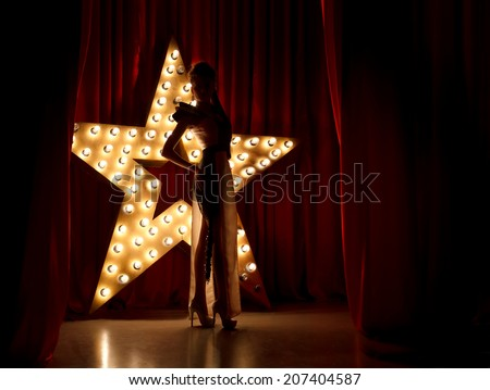 Fashion woman on stage.Red velvet curtain  with brodway star on background  - stock photo