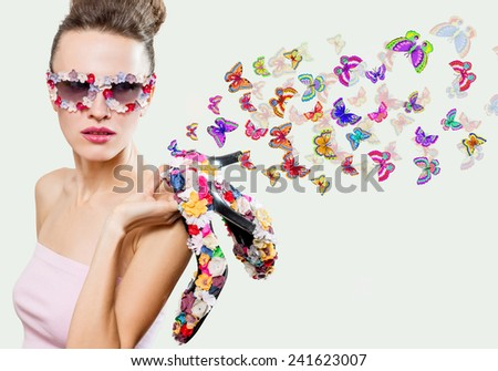 Fashion woman with flying butterflies over light background. Summer vacation concept - stock photo